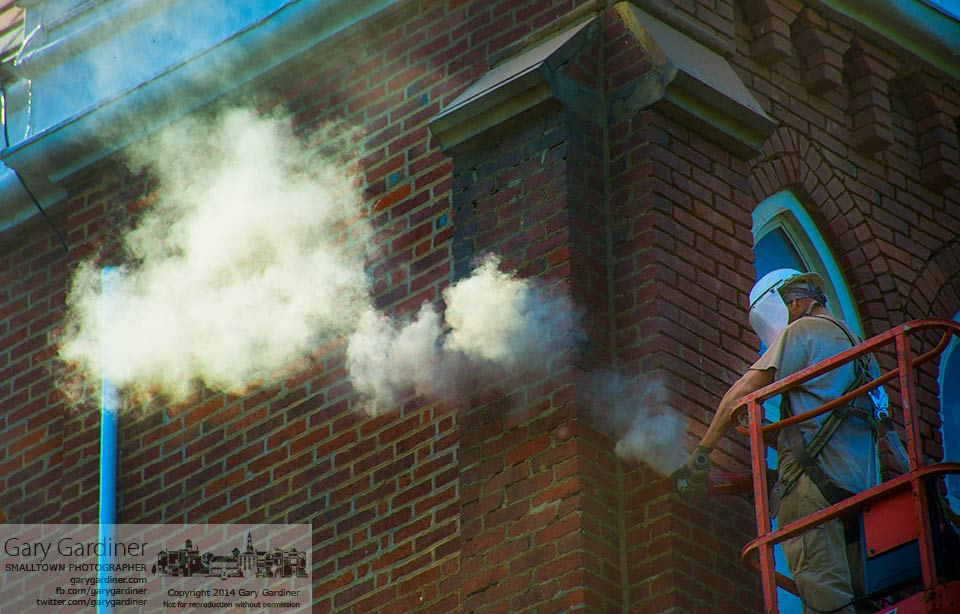A cloud of mortar dust floats away from one of two workers repairing mortar joints on Towers Hall at Otterbein University. My Final Photo for June 3, 2014.