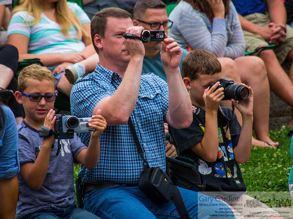 A man and two boys use video and digital cameras to record the concert performance by students at Otterbein University's Summer Music Experience camp. My Final Photo for July 18, 2014.