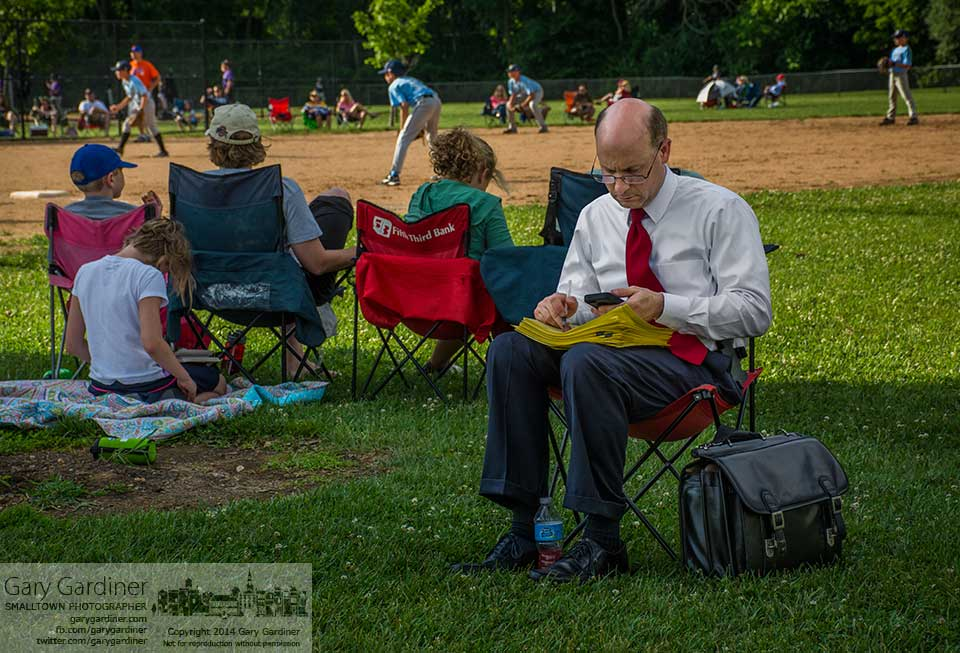 A father checks his phone while working with a stack of papers at the start of a baseball game at Huber Village Park. My Final Photo for July 8, 2014.