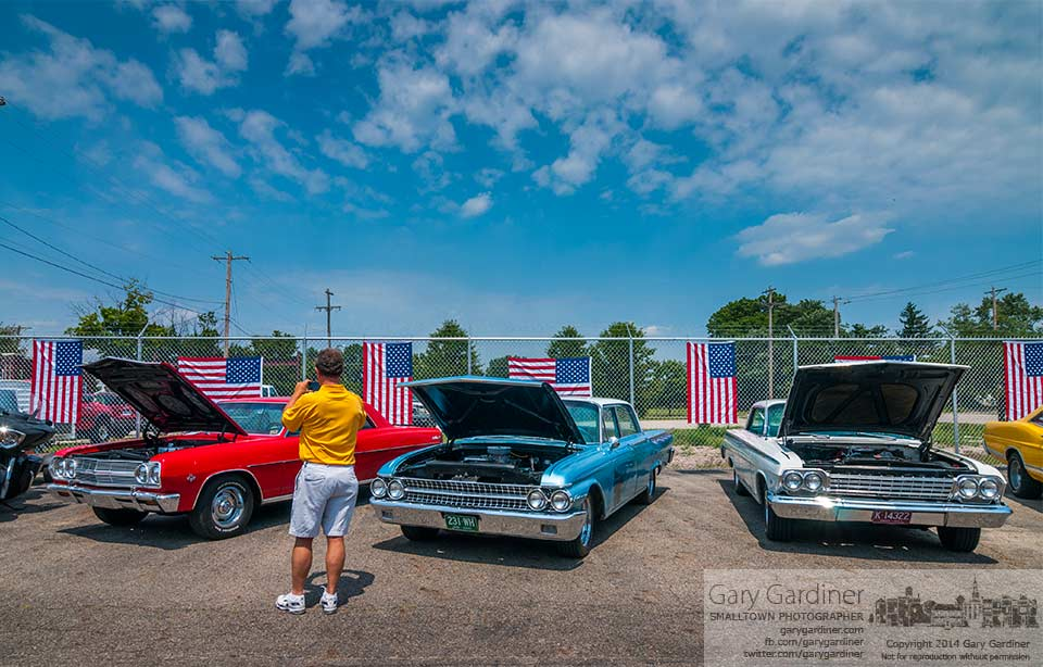 A vintage car enthusiast photographs car displayed at the Wrench 'n' Roll garage grand opening. My Final Photo for July 26, 2014.