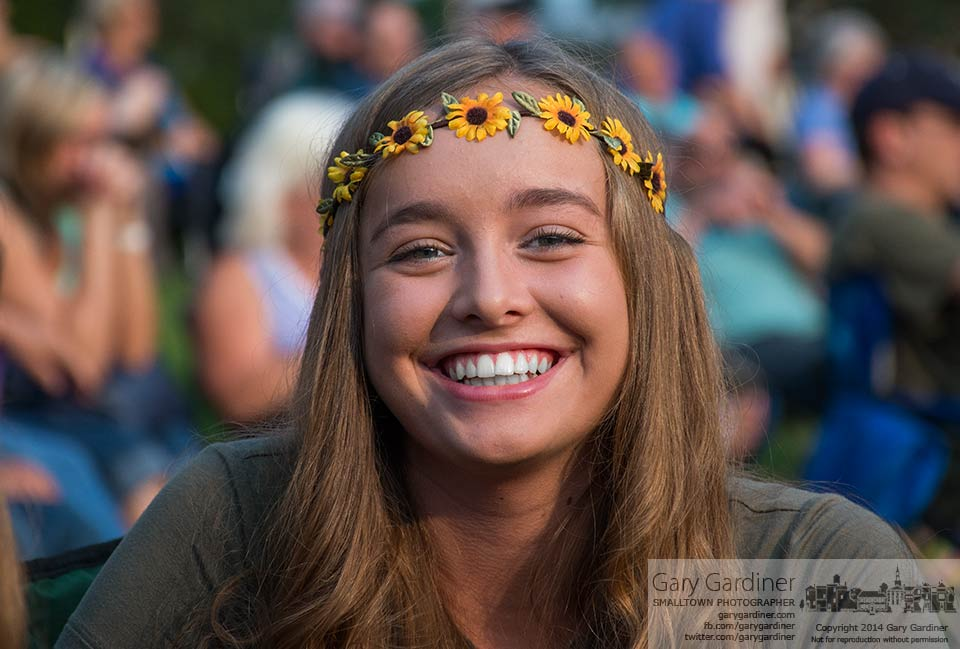 A young girl wearing flowers in her hair smiles during a break in The British Invasion concert at the amphitheater in Alum Creek Park. My Final Photo for July 20, 2014.