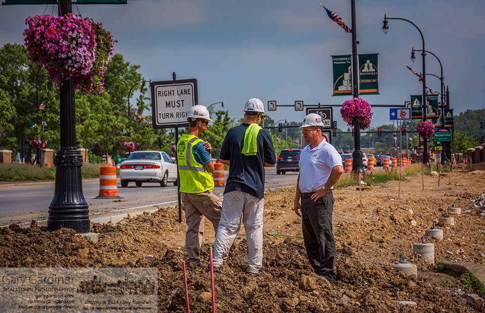 A trio of construction workers, supervisors, and inspectors, discuss a section of the right-of-way under construction at the entrance to Westerville on South State Street where construction of a revitalized roadway nears completion. My Final Photo for July 1, 2014.