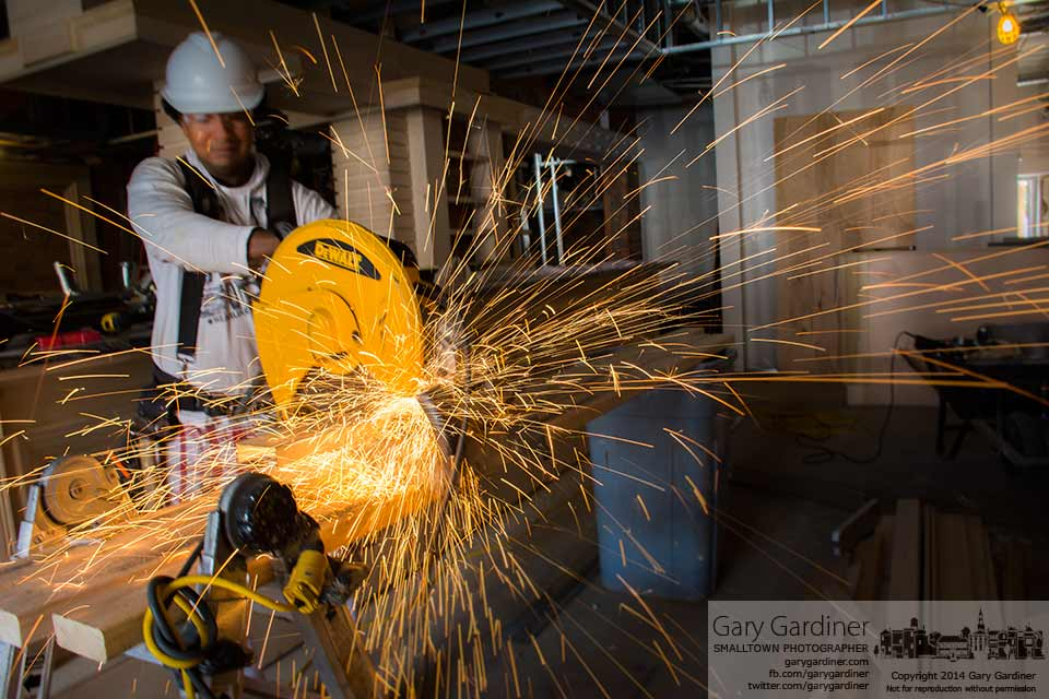 Sparks fly from a metal cutting saw as workers install steel studs for the ceiling tiles at Kolbe restaurant  on State Street in Uptown Westerville. My Final Photo for July 29, 2014.