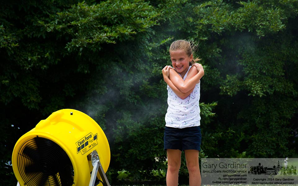 A young girls stands in the water spray from a cooling water fan at the Westerville Music and Arts Festival. My Final Photo for July 12, 2014.