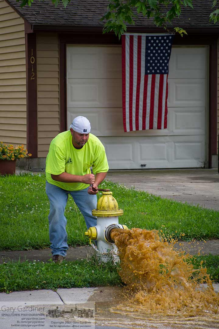A city worker clears a fire hydrant line as part of a city-wide water testing program. My Final Photo for July 14, 2014.