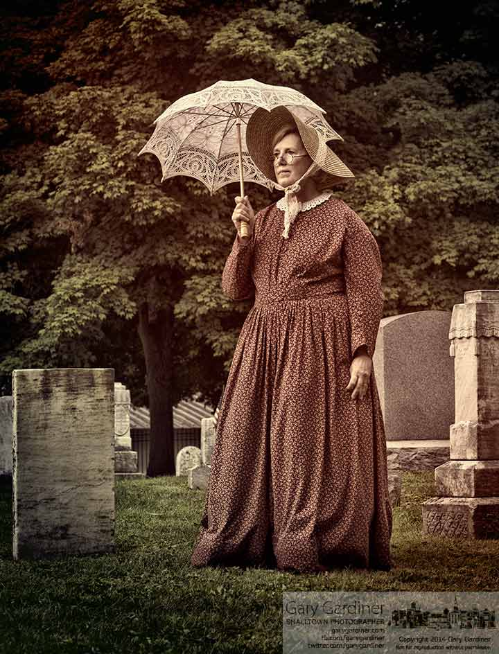 A reenactor stands with a sun umbrella in Old Methodist Cemetery during Sunday's Tapestry Of A Town historical tour of historic Uptown Westerville.. My Final Photo for July 27, 2014.