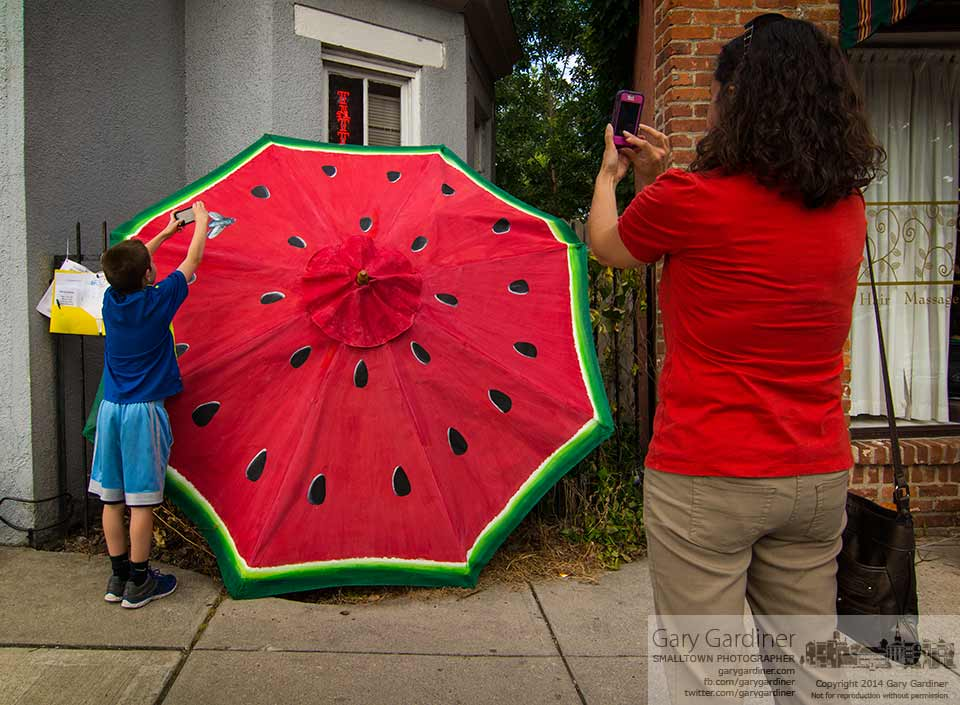 Mother and son pause for photos of the watermelon umbrella displayed in Uptown Westerville as part of a charity fundraiser. My Final Photo for July 11, 2014.