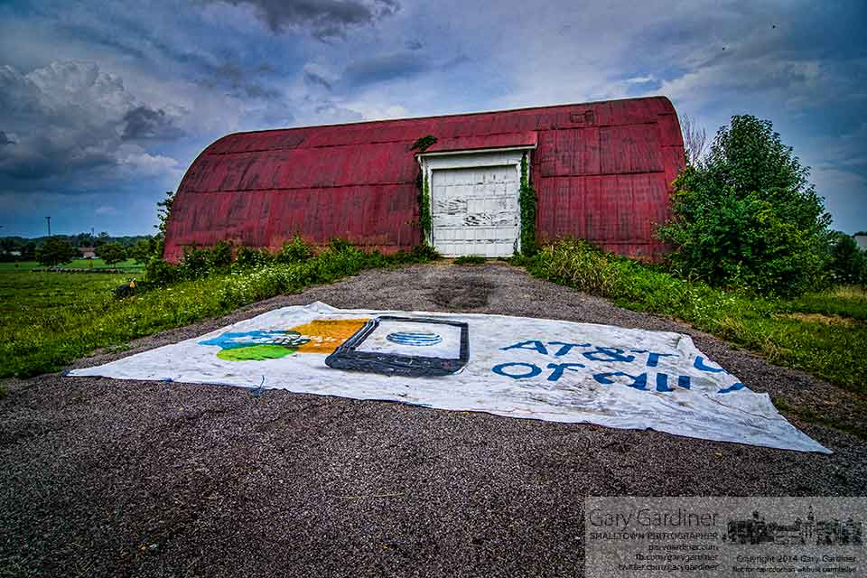 A billboard advertisement canvas used as a farm tarp sits in front of the barn at the Braun Farm. My Final Photo for August. 11, 2014.
