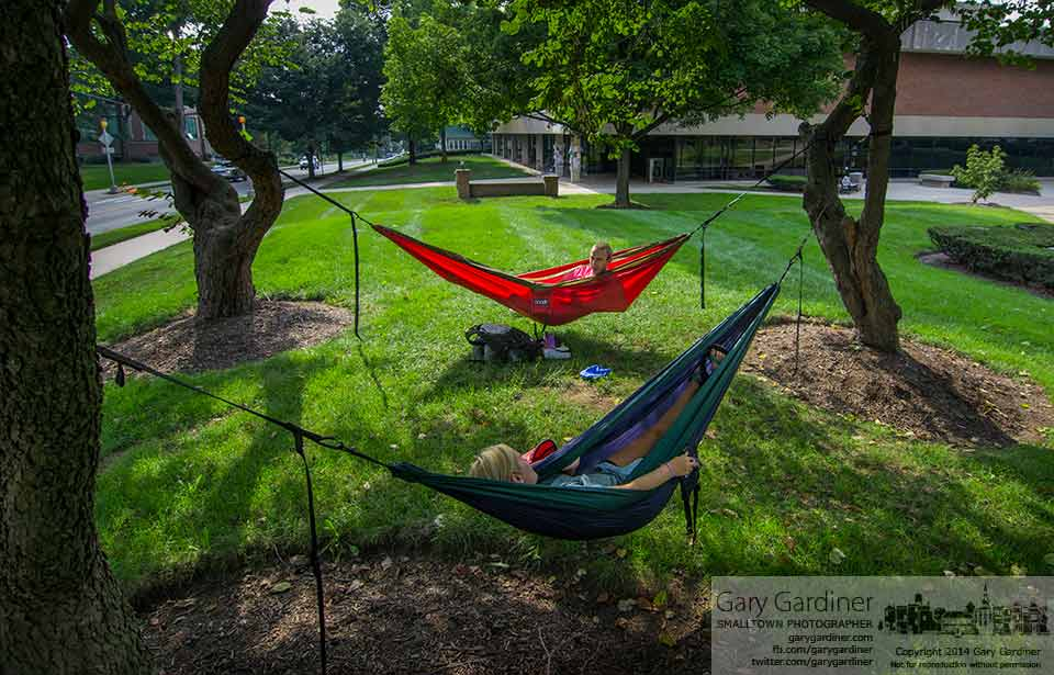 A pair of Otterbein students use hammocks for relaxation and a slightly different study environment in the trees at the corner of Main and Grove street on the campus. My Final Photo for August 26, 2014.