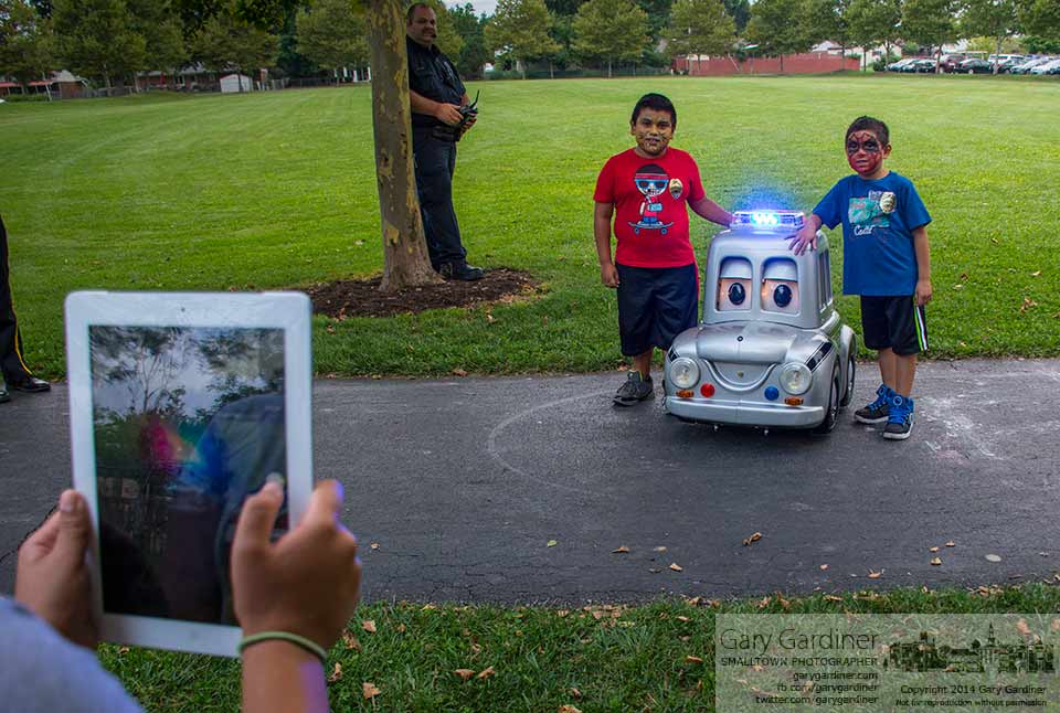 "A pair of youngsters with painted faces pose with ""PC,"" the Westerville police department's remote-controlled car during National Night Out at Huber Village Park. My Final Photo for August 5, 2014."