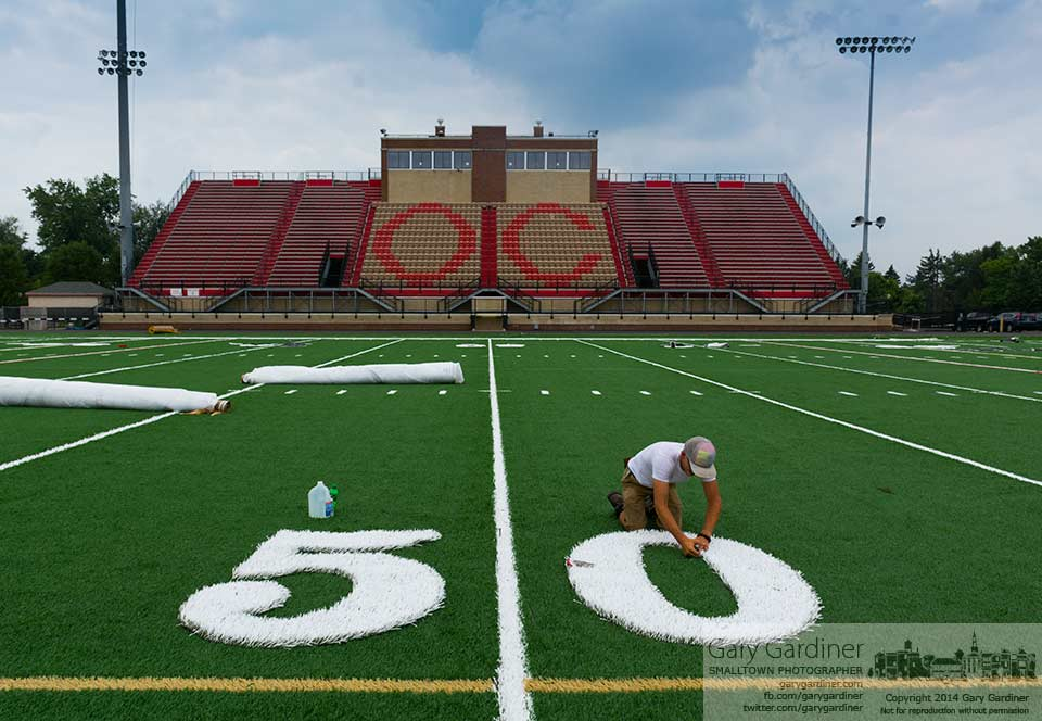 A worker installs the 50-yard line markers into a cutout section of the new artificial surface at Ballenger Field at Otterbein University. My Final Photo for August 18, 2014.