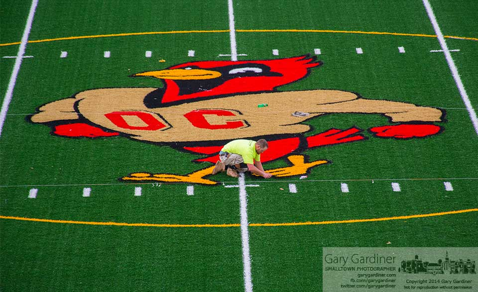 Phil Hilt of The Motz Group cuts away the green surface of the Otterbein football field where the school's oversize logo will be installed as part of the stadium's renovation. My Final Photo for August 21, 2014.