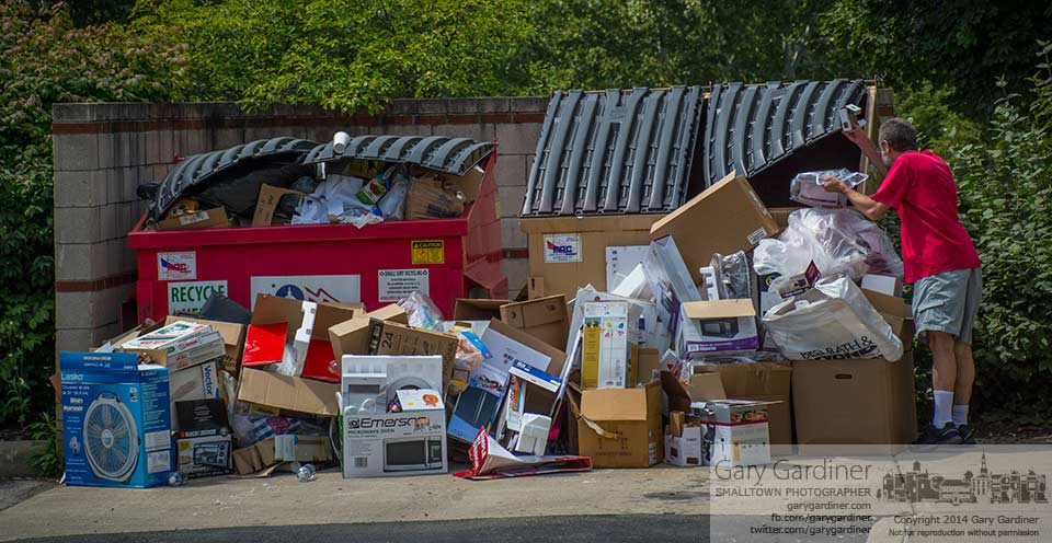 An Otterbein student's parent carries boxes to the overflowing trash bins in the parking lot as students moved into dormitory rooms on their first day at the university. My Final Photo for August 20, 2014.