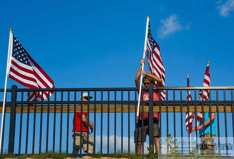 Workers setup flags spanning both sides of the Main Street Bridge as part of the Travis Manion 5K race set for Saturday morning. My Final Photo for Sept. 5, 2014.