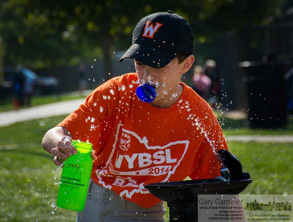 A young baseball player struggles to fill his water bottle before a game at Huber Village Park. My Final Photo for Sept. 18, 2014.