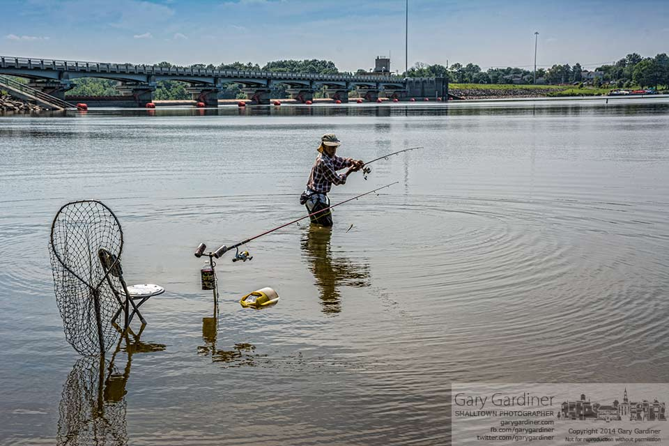 A fisherman wades into Hoover Reservoir to cast one of his lines further  into the lake hoping to take home a healthy catch. My Final Photo for Sept. 4, 2014.