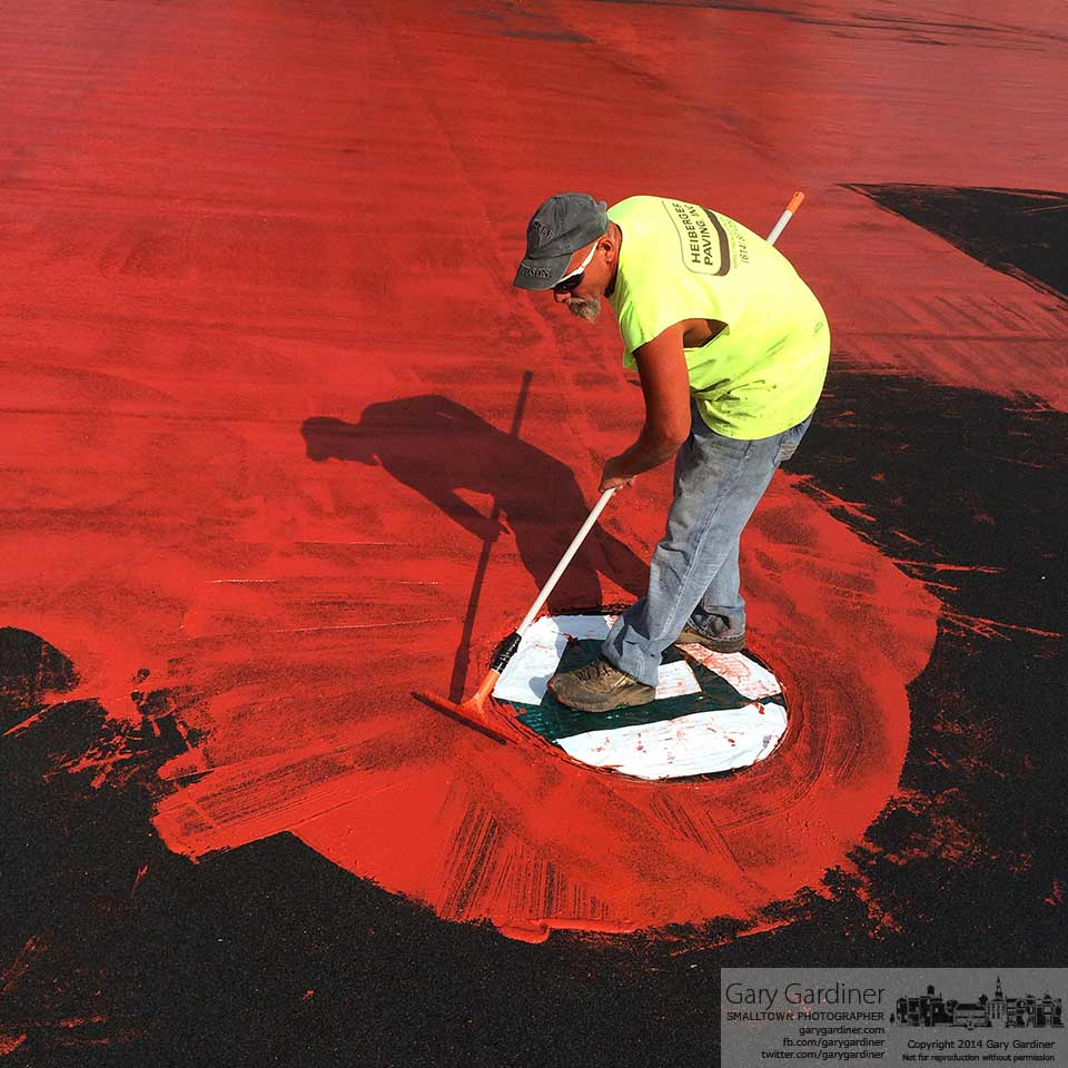 A worker squeegees sealant around a drain at the edge of the track at Otterbein University  in preparation for the final layer of cardinal red rubber to be laid on the renovated surface. My Final Photo for Sept. 9, 2014.
