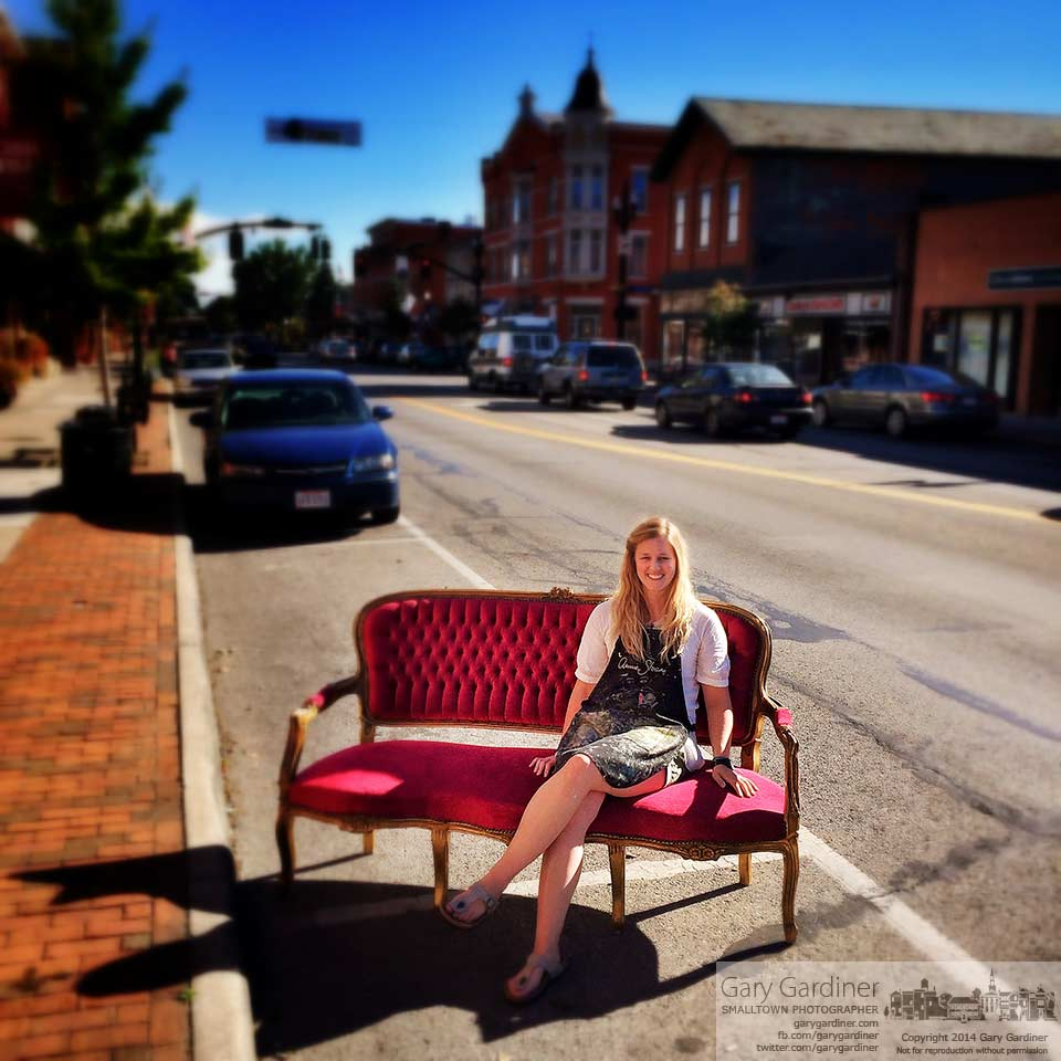Amy Winter, the owner of Edwin Loy Home in Uptown Westerville, sits in the red velvet c ouch she bought for her home decor and vintage items store. My Final Photo for September 24, 2014.