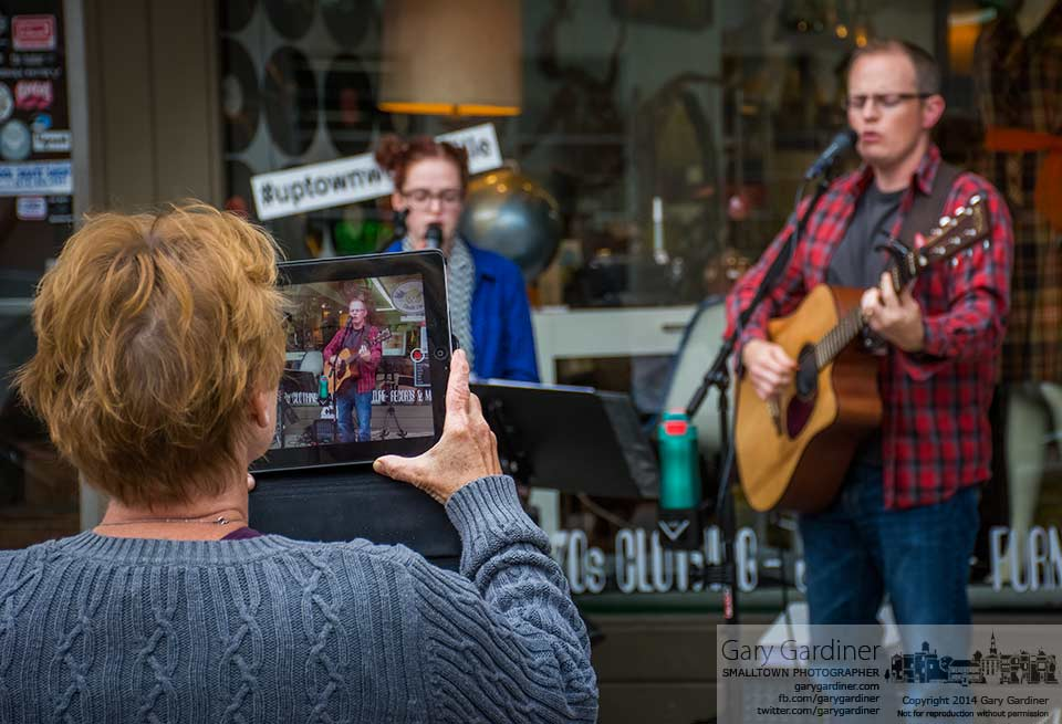 A woman  uses her iPad to record her family's performance in front of Cinda Lou's in Uptown Westerville as part of the merchant's Friday night music celebration. My Final Photo for Sept. 12, 2014.