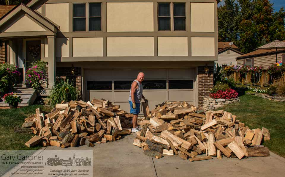A man prepares  stack two cords of wood after it was delivered to his daughter's house in an early preparation for winter. My Final Photo for Sept. 28, 2014.