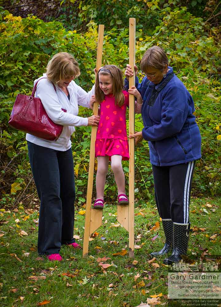 Two women help a young girl steady herself on a pair of stilts at the Ned Moshe Apple Butter Festival. My Final Photo for Oct. 5, 2014.