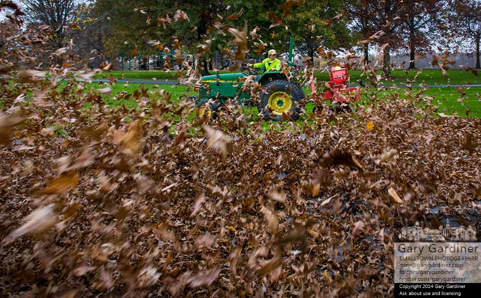 A Sharon Woods Park worker uses a blower towed behind a tractor to clear fallen leaves from the picnic and playground area of a section of the park. My Final Photo for Oct. 28, 2014.
