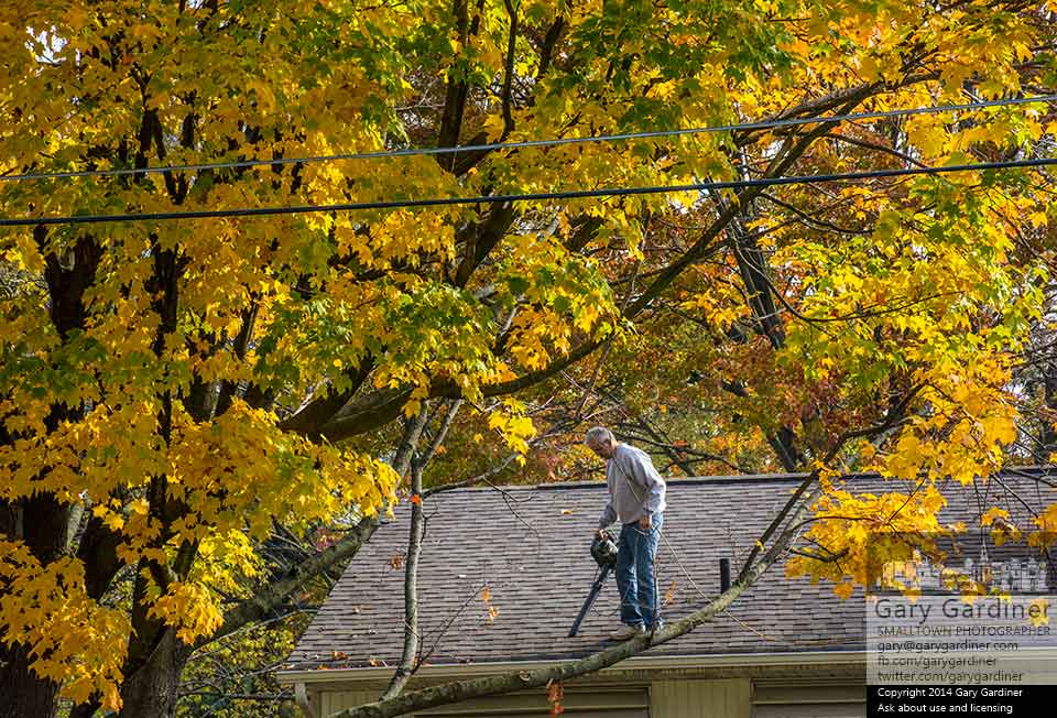 A man uses a leaf blower to clear maple leaves from his gutters under the canopy of unfallen leaves from the same trees that filled the gutters. My final Photo for Oct. 25, 2014.