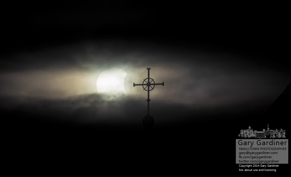 The lunar eclipse slides between two clouds behind the cross at the top of St. Paul Catholic church. My Final Photo for Oct. 23, 2014.