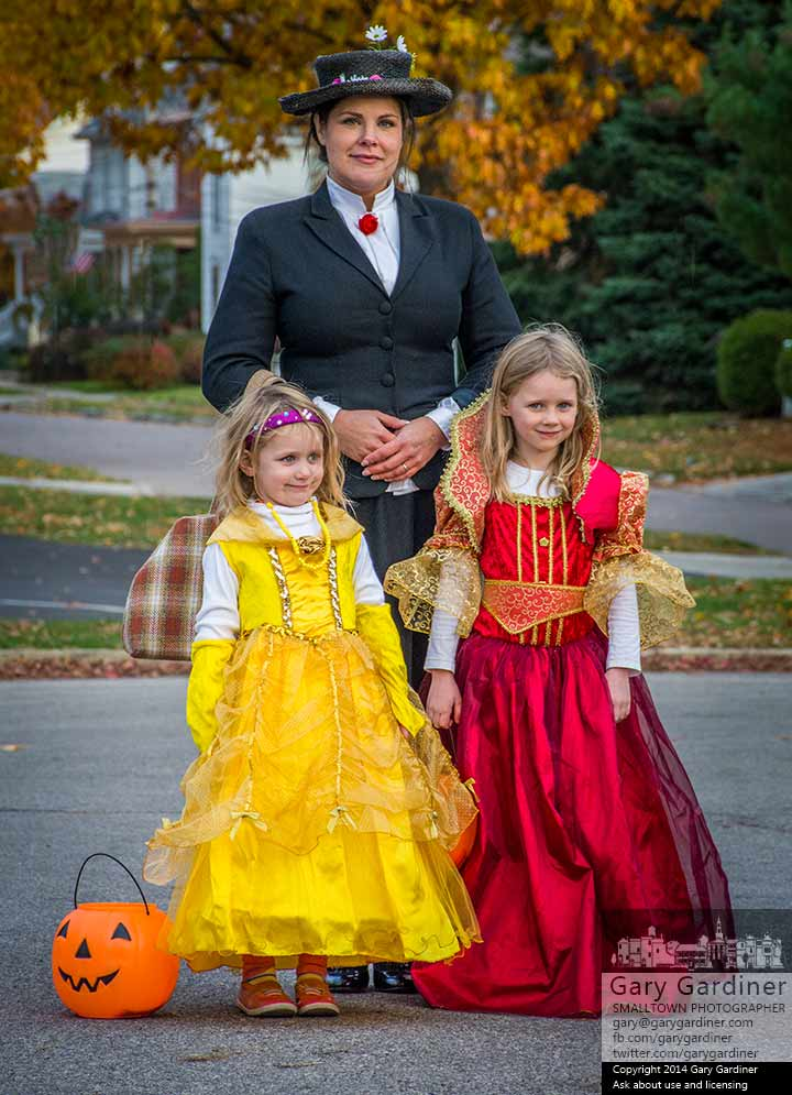 Sisters dressed at Disney princesses pose with an Uptown Farmers Market vendor dressed as Mary Poppins to celebrate the market's final day of the season at Halloween. My Final Photo for Oct. 29, 2014.