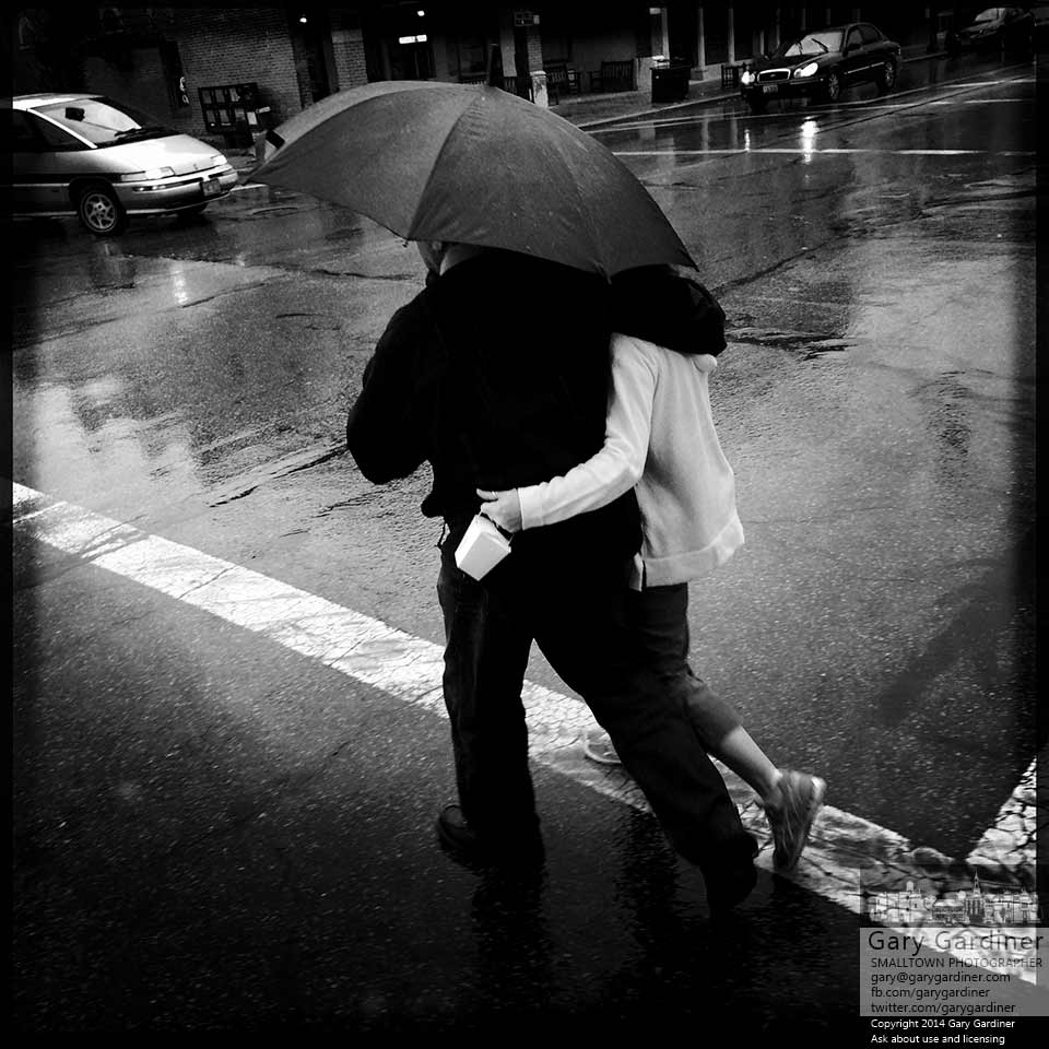A couple wraps their arms around each other to share an umbrella as they cross State Street in Uptown Westerville during a late afternoon rain storm. My Final Photo for Oct. 14, 2014.