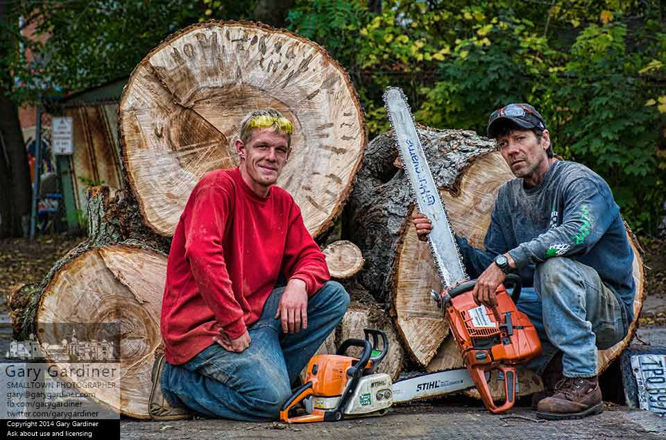 Tree cutters Jarod Holland and Brian Doucette pose with their saws and the tree they felled in a day long job in Uptown Westerville. My Final Photo for Oct. 11, 2014.