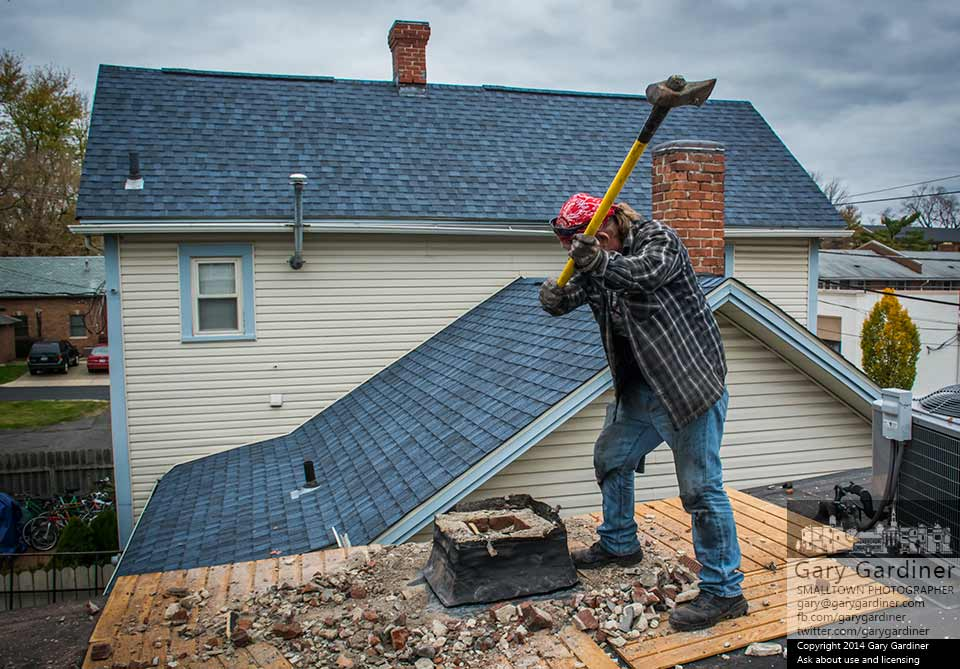 John G'Nosa uses a sledge to break away the last section of bricks on a damaged and leaking chimney he removed from Dave's Barber Shop in Uptown Westerville. My Final Photo for Oct. 30, 2014.