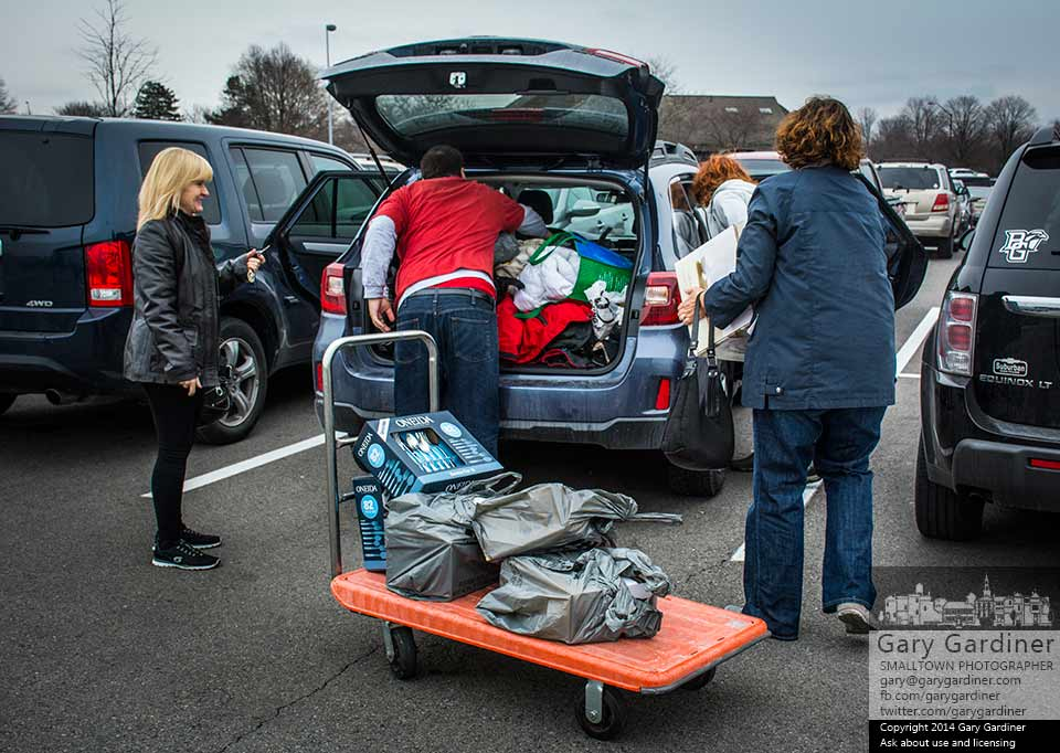 A trio of shoppers gets assistance from a store employee unloading the utility cart full of gifts they bought at Kohls in Westerville. My Final Photo for Nov. 29, 2014.