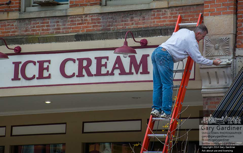 A maintenance man brushes away the oxidized surface pf concrete on the front of Graeter's Ice Cream in Uptown Westerville during fall cleanup at the store. My Final Photo for Nov. 8, 2014.