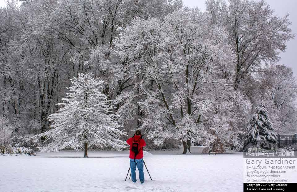 A photographer places his tripod and camera in a small field in Inniswood to photograph snow covered trees in the park. My Final Photo for Nov. 17, 2014.