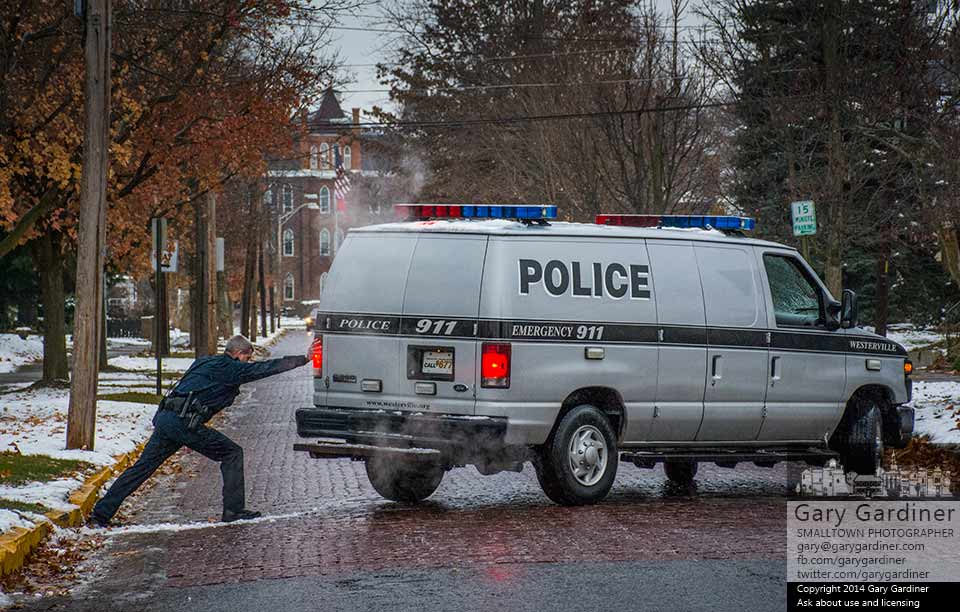A Westerville police officer pushes the rear of his van as his partner attempts to clear it from the icy brick surface of West College where it spun out less than 100 feet from the entrance to the police parking lot entrance. My Final Photo for Nov. 22, 2014.