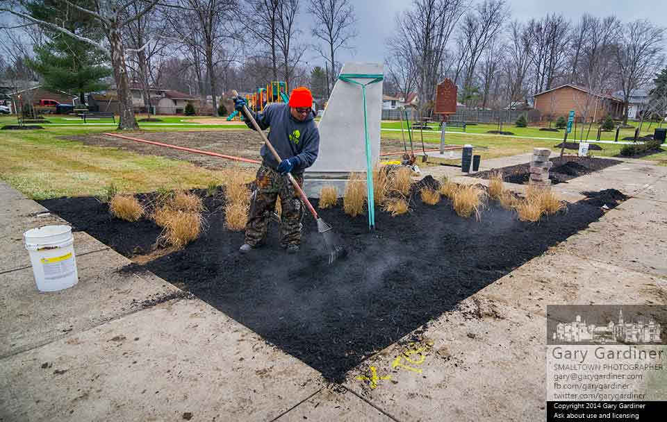 A landscaper rakes steaming  mulch into one of the new garden spaces at Phelps Acre Park in Blendon Township where renovations include new playground equipment and structure changes. My Final Photo for Dec. 9, 2014.