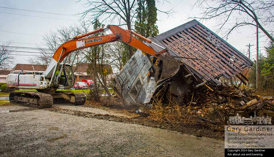 A one-man, one-machine demolition crew topples the walls of a house on East College completing the demolition of the building. My Final Photo for Dec. 16, 2014.