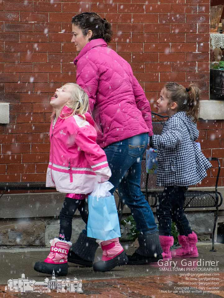 Two young girls take advantage of large snow flakes to try and grab a taste of snow as mom guides them to a birthday party in Uptown Westerville. My Final Photo for Jan 25, 2015.