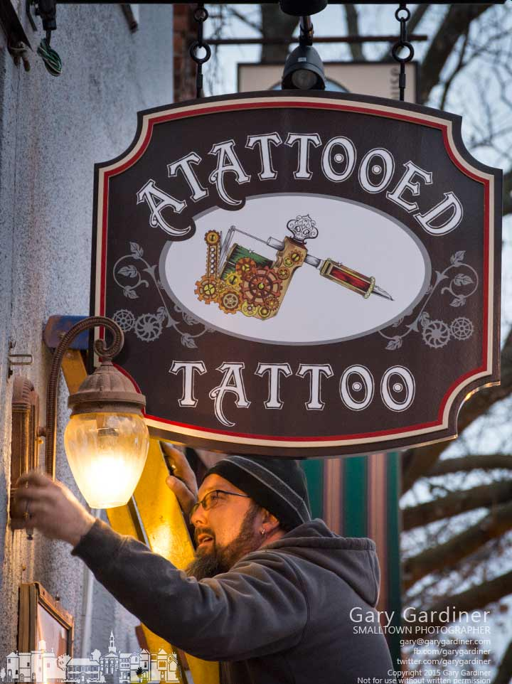 A worker installs the new sight for Atattooed Tattoo shop and removed the obstructing light at the store on State Street in Uptown Westerville. My Final Photo for Feb. 11.