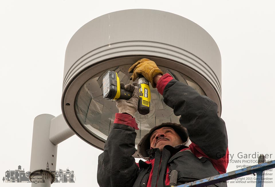 A lighting technician secures the cover to a parking lot light after changing bulbs. My Final Photo for Feb. 3, 2015.