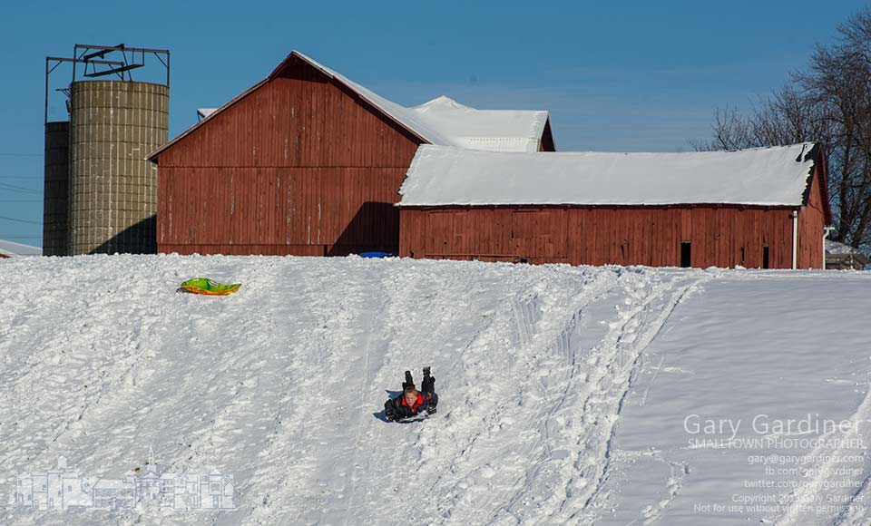 A youngster rides a plastic disk down the snow-covered hill behind his neighbor's barn on a bitterly cold afternoon. My Final Photo for Feb. 24, 2015.