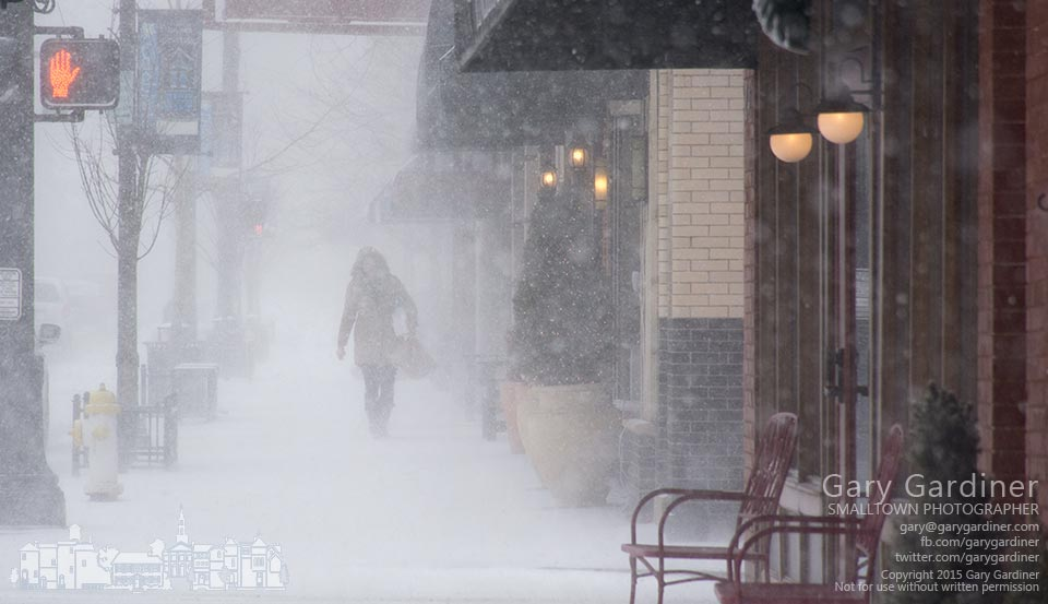 A blast of wind-driven snow obscures the view down a sidewalk for an early shopper in Uptown Westerville. My Final Photo for Feb. 12, 2015.