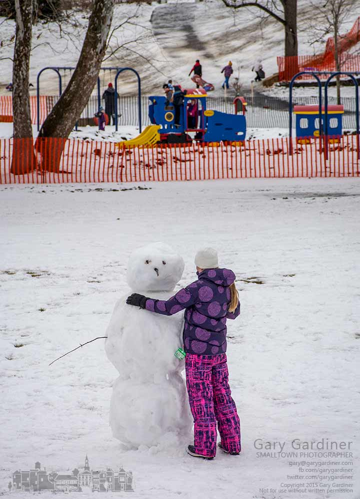 A woman makes the final adjustments to the shape of the snowman that she and her friends made at Alum Creek Park in Westerville. My Final Photo for Feb. 1, 2015.