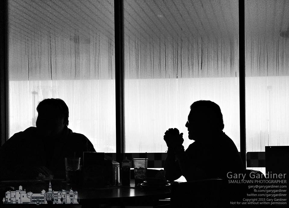 Two men talk  during their lunch inside a restaurant whose windows are covered in condensation from steam used to heat the serving line. My final Photo for Feb. 26, 2015.