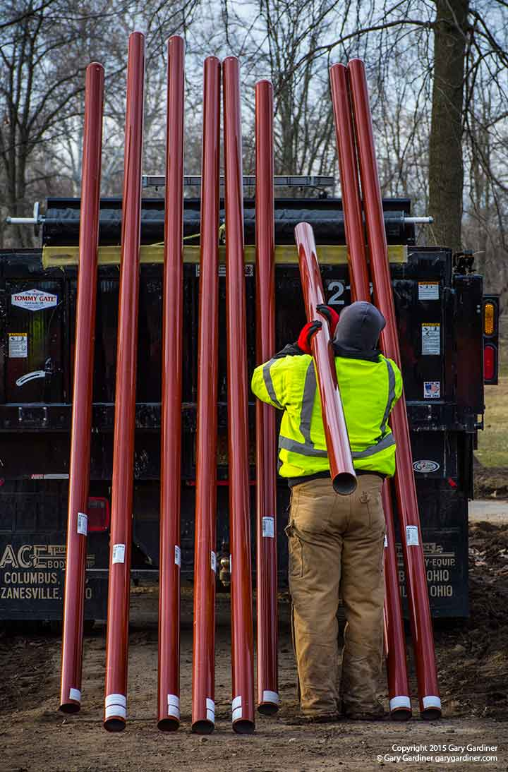 A city worker carries one of the new poles to be used to support new playground equipment at Alum Creek Park. My Final Photo for March 19, 2015.