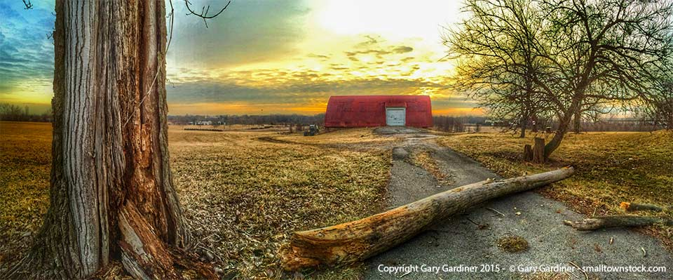 The limb from a damaged tree lies across the roadway leading to the barn at the Braun Farm after it suffered through the harsh winter. My Final Photo for March 16, 2015.