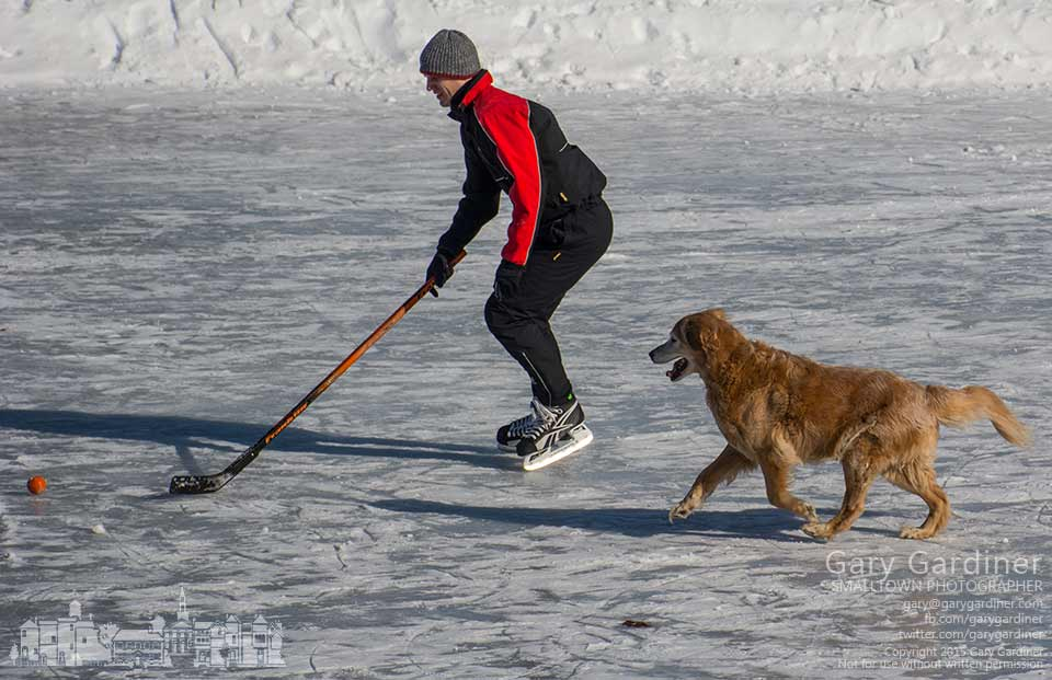 Man and dog chase the same orange ball across the ice at Metzger Park in Westerville. My Final Photo for Feb. 28, 2015.
