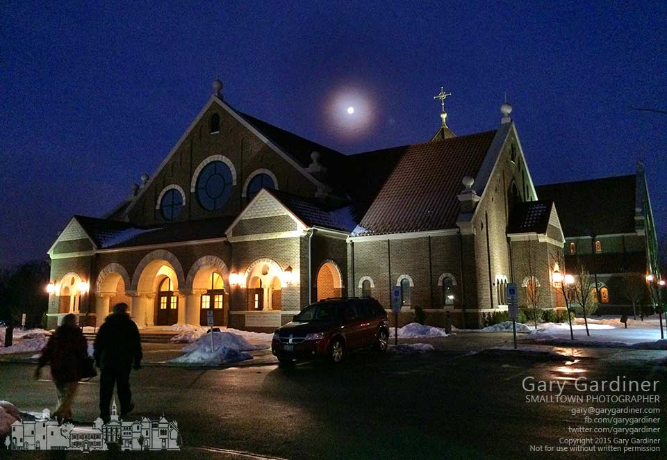 A waning moon glows behind a cloud over St. Paul Church in Westerville as two parishioners arrive for the early Mass on the first day of daylight savings time. My Final Photo for March 8, 2015.