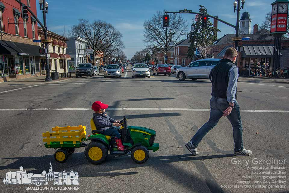 A father leads his driving an electric toy John  Deere tractor and wagon across State Street in Uptown Westerville. My Final Photo for March 25, 2015.